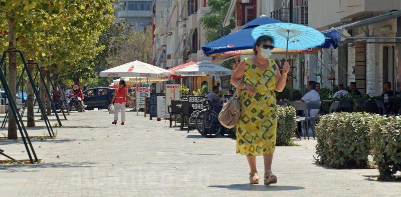 Frau auf einer Strasse in Albanien schützt sich mit Maske vor COVID-19 und mit einem Schirm vor der Sonne